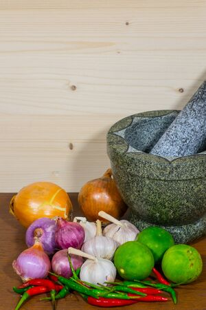 fragrant: Mortar, lemon, pepper, onion and garlic, cooking on wooden background