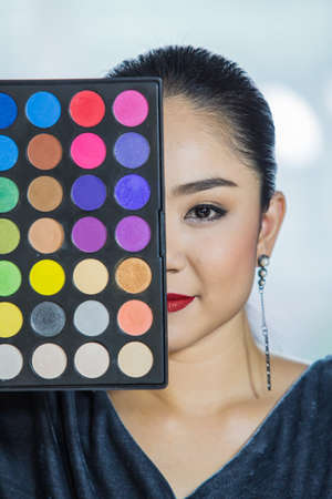 Brunette woman applying make up and holding a brush And color in the make-up.shadow kit with brush for make-up