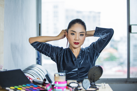 Portrait of beautiful young Asian woman combing her hair Stock Photo