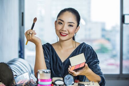 Brunette woman applying make up  closeup portrait of woman with makeup brush near face Stock Photo