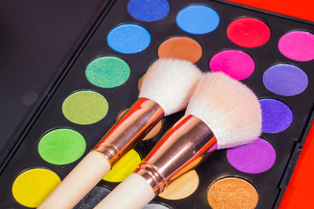 Set Colorful Make up Brush and cosmetic isolated on a red background.