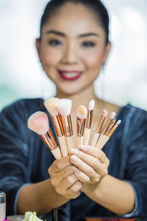 Portrait of a young gorgeous brunette woman with makeup tools, brushes.Beauty Girl with Makeup Brushes. Perfect Skin. Applying Makeup