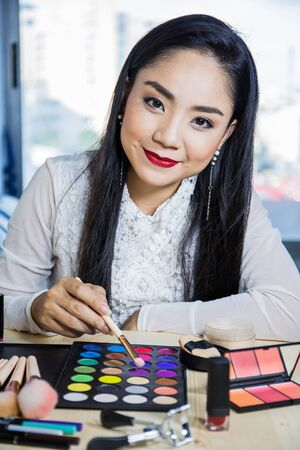 Portrait of beautiful young Asian woman ,Brunette woman applying make up  Is using makeup equipment