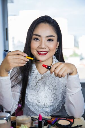 Portrait of beautiful young Asian woman ,Brunette woman applying make up in hand with mouth lipstick