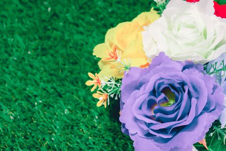 Beautiful fake flower vases on a grassy background. Stock Photo