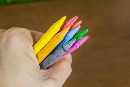Hand holding a colorful candle colored pencils.