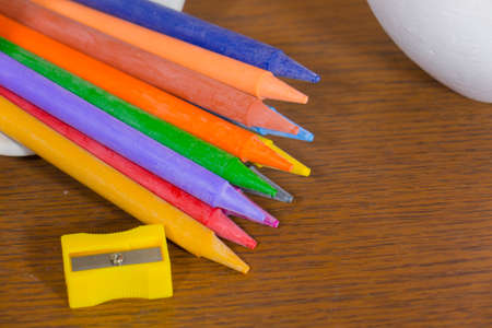 colorful crayons with pencil sharpener on wooden background