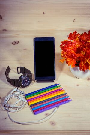 Many colorful crayons on wooden background with clock, phone, earphone to create artwork. Stock Photo