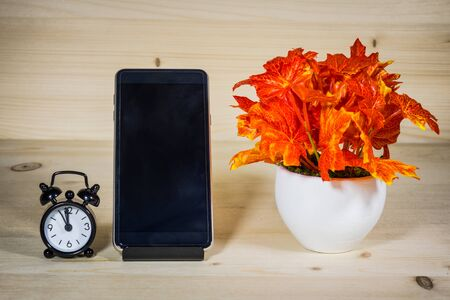 Wooden table with telephone, clock and the vase, then relax.