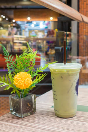 Green tea is cool, put the glass on a flower vase on a wooden background table.