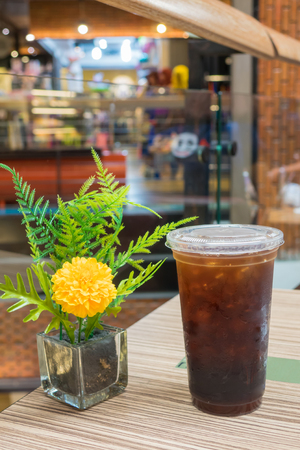 Cold coffee in glass with flower vase on wooden table Stock Photo