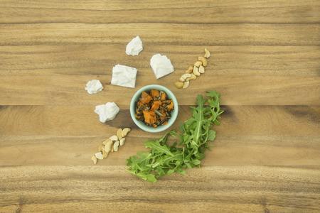 Ingredientes de queso feta, rúcula, cacahuetes, arroz salvaje y zanahoria en tabla de cortar de madera Foto de archivo - 72850549