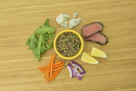 Lentil, Steak, Carrot, Red Onion, Lemon, Arugula and Bleu Cheese ingredient on bamboo cutting board