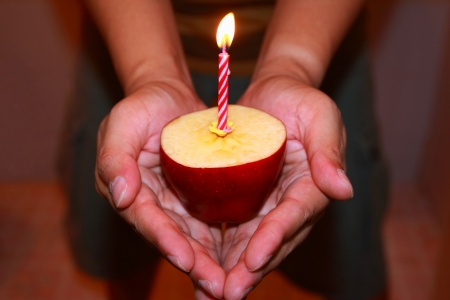 Birthday candles in apples on hands Stock Photo