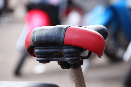 exert: Red and  black bicycle saddle close-up