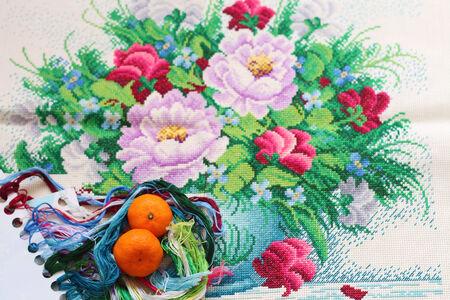 Orange on a Cross stitch flower Stock fotó