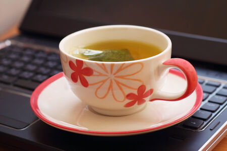 potation: Hot tea is placed on a black notebook Stock Photo