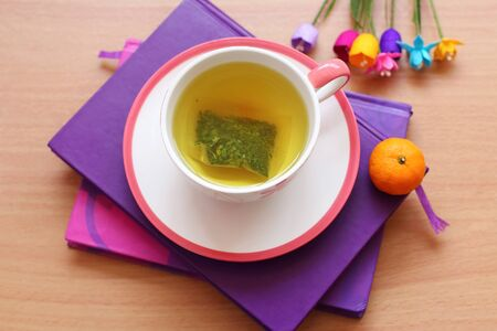 Hot tea and orange on the purple book photo