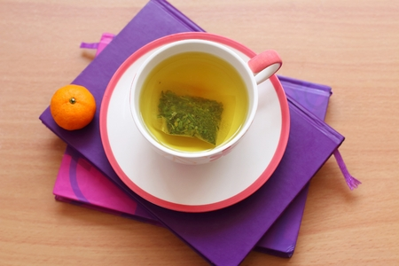 tea breaks: Hot tea and orange on the purple book