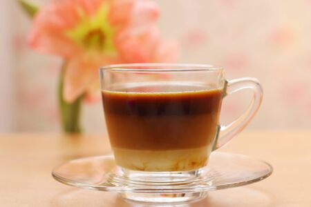 potation: Hot coffee on the table and flower background Stock Photo