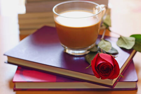 Hot coffee and red rose put on the purple and wooden table photo