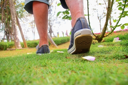 People wearing white sneakers are moving in the grass photo