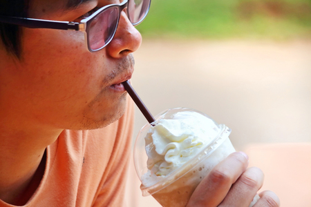 Man is drinking iced coffee photo