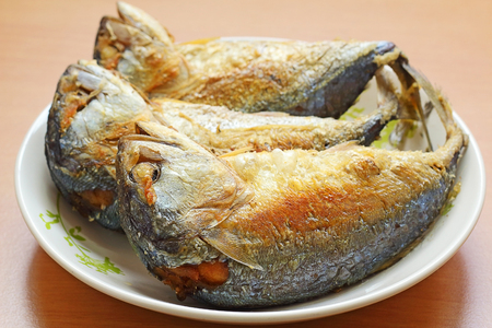Fried Mackerel in plate on wooden table photo