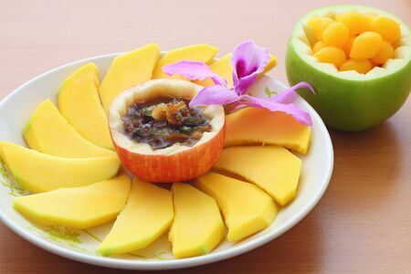 mango with sweet fish sauce and Thai dessert on the wooden table photo