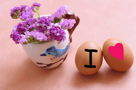Purple flowers in a vase and egg on the wooden table photo