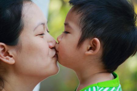 mama e hijo: Madre besando a su hijo de cerca Foto de archivo