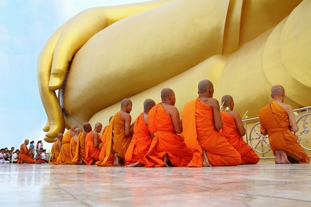 ang thong: Ang Thong, Thailand-July 11,2014: Buddhists and monks walk with lighted candles clockwise round the temple, Asaha Puja Day and the beginning of Buddhist Lent, at Wat Muang- Ang Thong, Thailand.