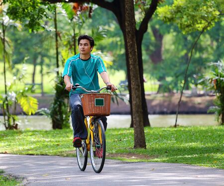 Asian men cycling in a park Stock Photo