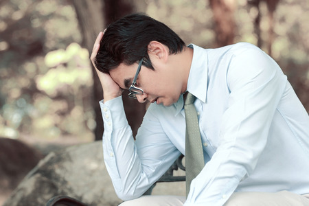 Asian men stress and hold the head with hand Stock Photo