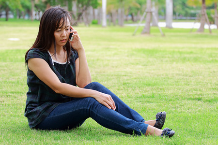 beautycare: Asian women talking mobile phone in the park