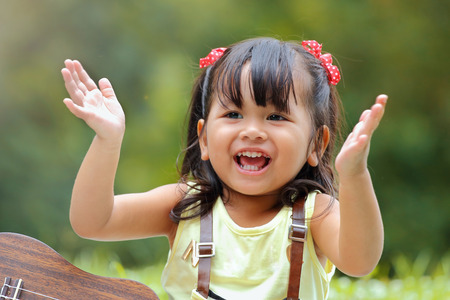 asian baby girl: Little asian girl was clapping happily in the park