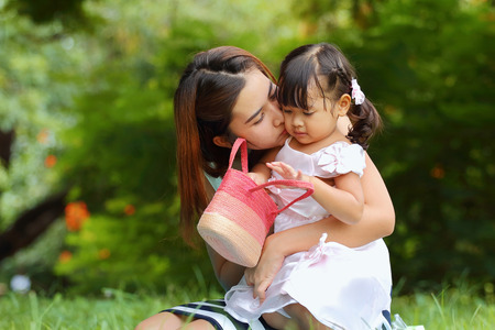 Asian family, Mother kiss her little daughter in the park. photo