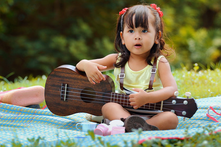 Little asian girl was playing ukulele happily in the park