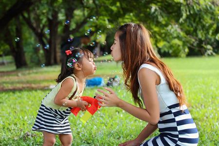 Familia asiática estaba jugando burbuja feliz en el parque Foto de archivo