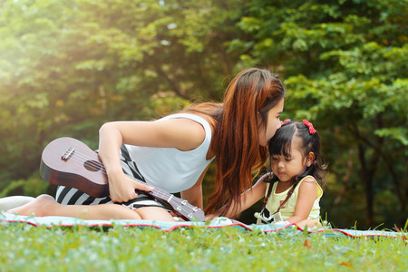 Asian family, Mother kiss her little daughter in the park.