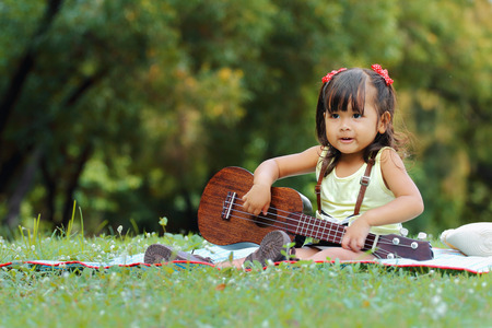 girl playing guitar: Little asian girl was playing ukulele happily in the park