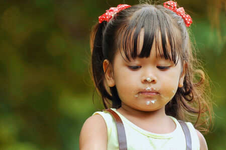 dowdy: Little asian girl was playing happily in the park, Candy dots on mouth