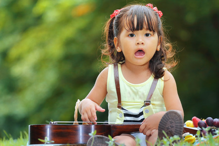 tercet: Little asian girl was playing ukulele happily in the park