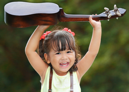 tercet: Little asian girl was smile and playing ukulele happily in the park