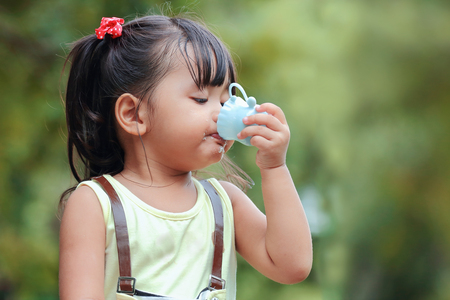 Little asian girl drinking water in park, close up photo