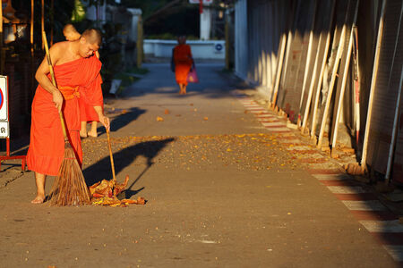 besom: Lamphun, Thailand - November 11:Unidentified Buddhist monk was street sweeping in the morning at Wat Phra That Hariphunchai, Thailand temple in Lamphun, Thailand on November 11, 2014 Editorial