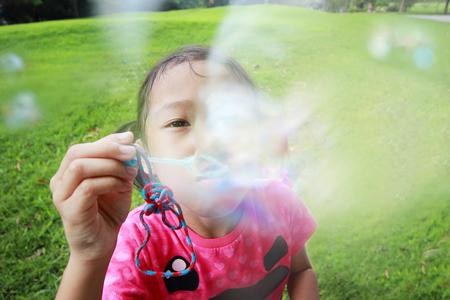 burbujas de jabon: Asia ni�a soplando pompas de jab�n, de cerca Foto de archivo