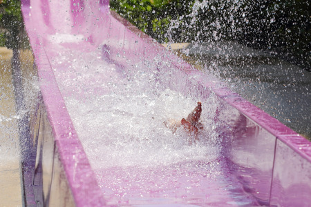 water park: The man enjoy playing slide in water park