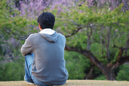 Asian man sitting in the Chinese-plum park, feel lonely Stock Photo