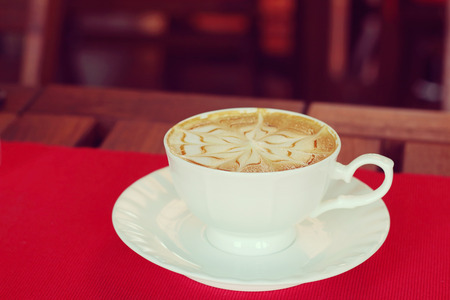 cosiness: Closeup, Hot Caramel Macchiato in white coffee cup, soft focus and blurred background, vintage tone